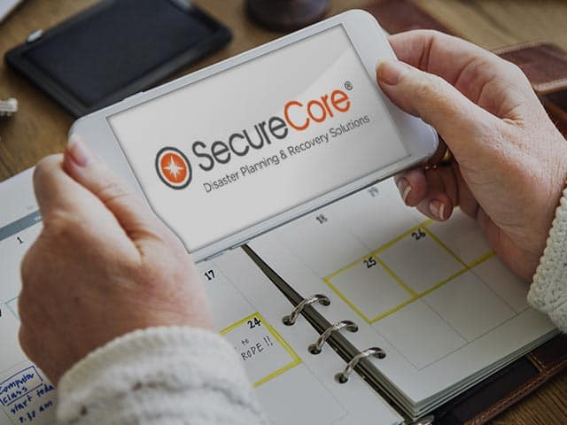 Person holding a cell phone with SecureCore's logo