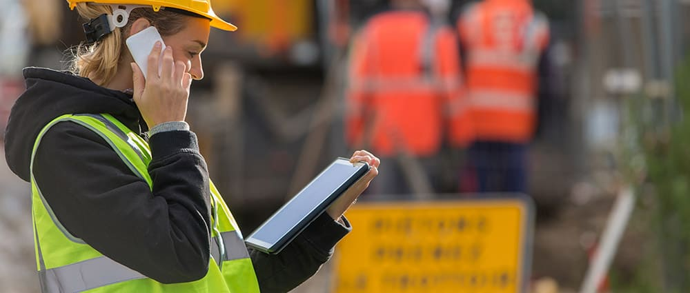 Worker wearing safety gear and accessing emergency response plans on a tablet with holding phone to ear